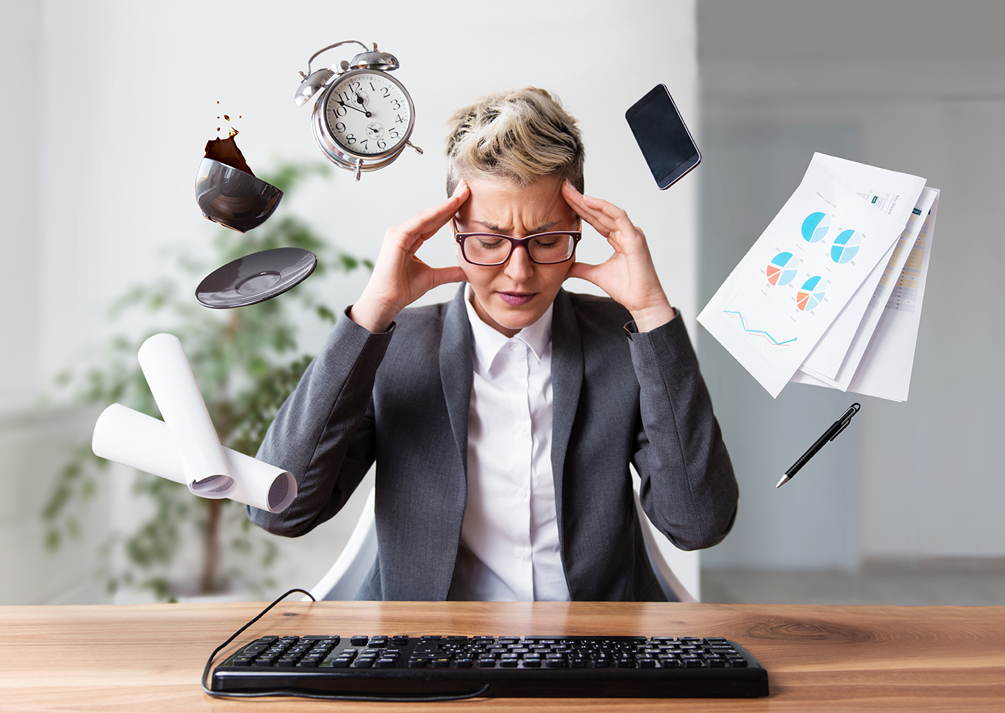 Mature women with pixie cut stressed out at work at her desk because she's trying to work and multi-tasking doesn't work