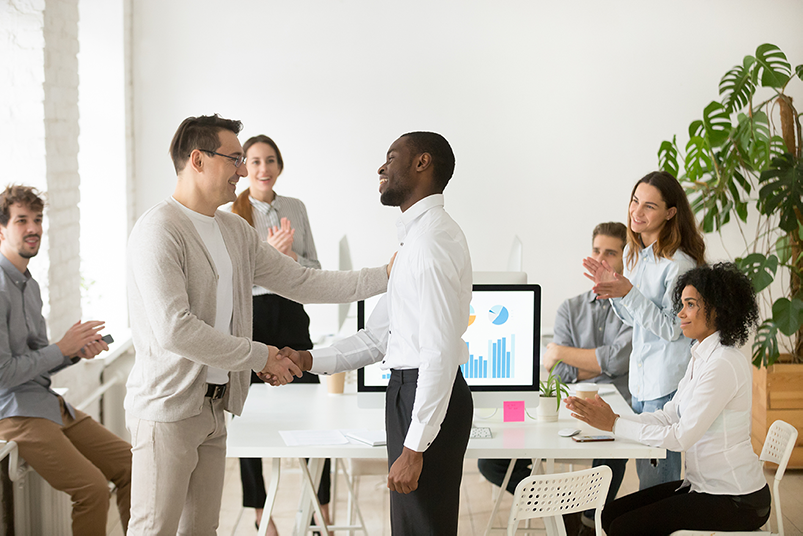 Young black man getting promoted and shaking hands with white men in front of his co-workers