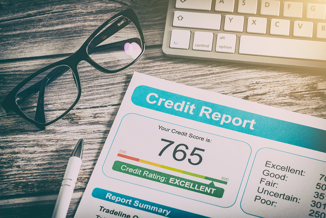 A credit report lying on desk with the number 765.