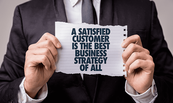 A man in a business suite holding a piece of paper that says a satisfied customer is the best business strategy of all