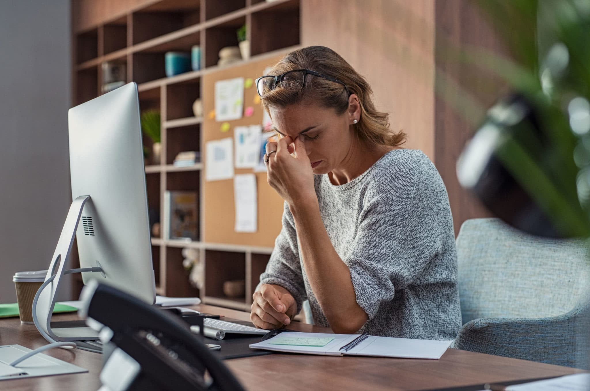 A woman experiencing headache due to work-related stress